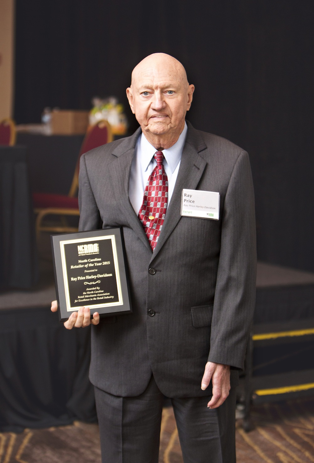 Ray Price of Ray Price Harley-Davidson with the award for 2015 Retailer of the Year from the N.C. Retail Merchants Association.